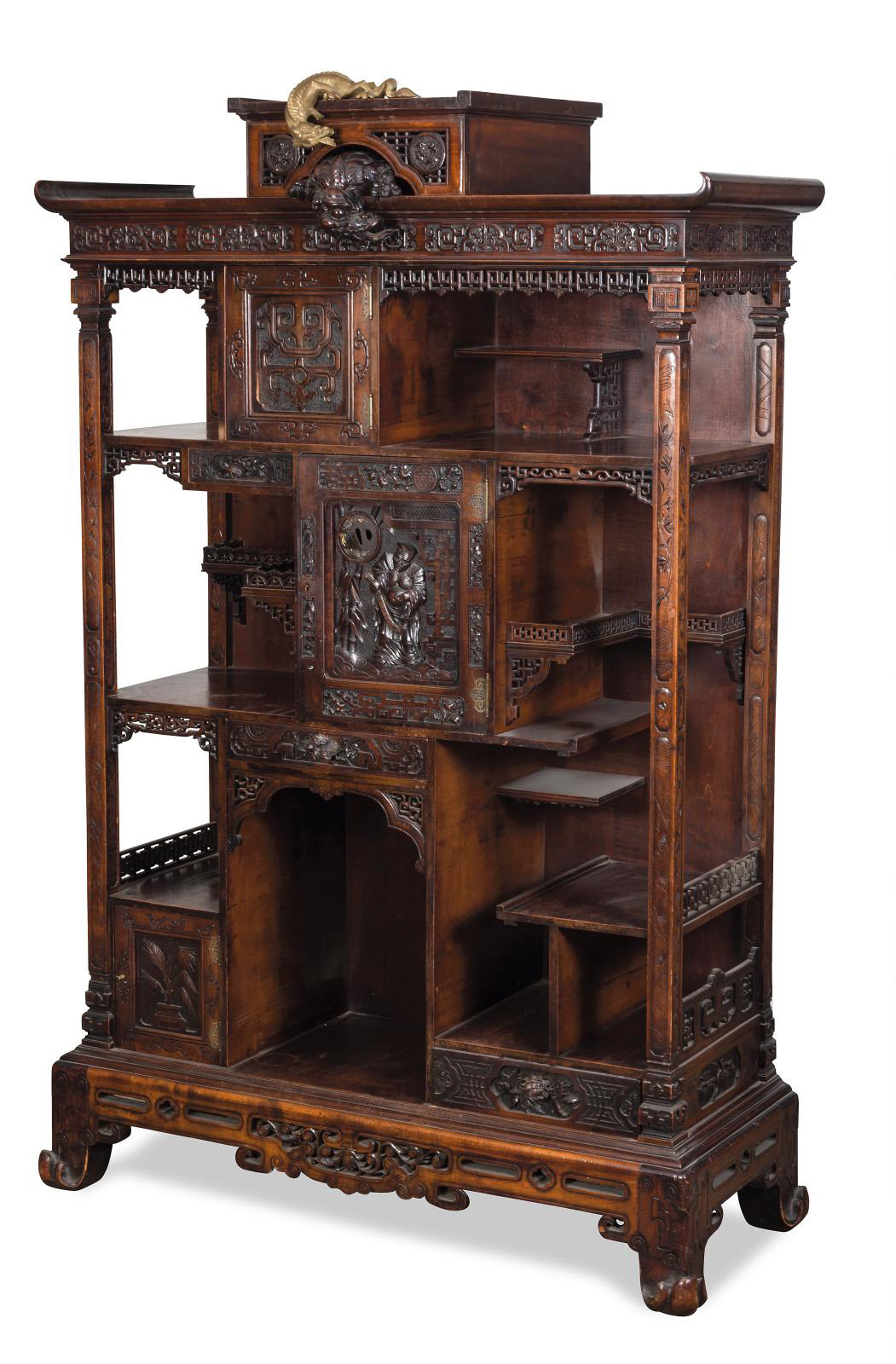 Carved, molded and patinated showcase cabinet in wood with two doors, one containing an openwork tsuba, and three drawers, Far-Eastern decoration of warriors, flowers, plants and openwork foliage, sides with unstructured shelves, a lively style base, pagoda cornice surmounted by two flying dragons, signed, 175 x 113 x 46 cm (68.9 x 44.5 x 18 in). Estimate: €1,000/1,500