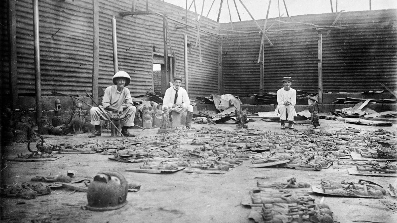 Interior of Oba's Compound Burnt During Seige of Benin City (present day Nigeria), with Bronze Plaques in the Foreground and Three British Soldiers of the Benin Punative Expedition 9-18 February 1897. Photographer Reginald Granville