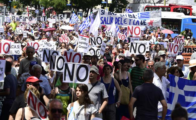 """People hold placards reading """"No"""" during a demonstration in support of Greece, in Madrid on July 5, 2015. (Agence France-Presse)"""